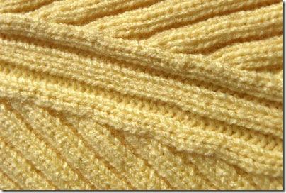 machine knitting closeup of raglan sweater armhole decreases